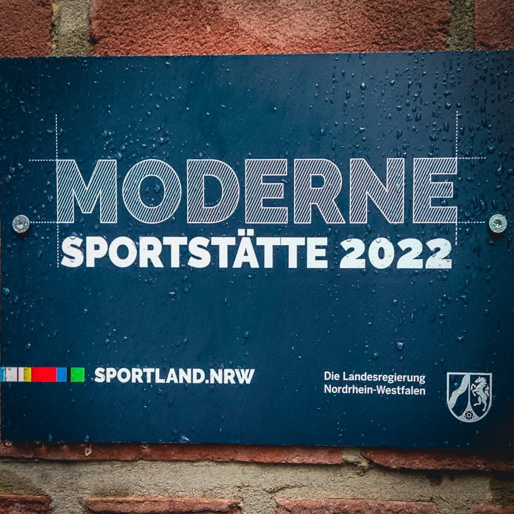 """Foto von einem neuen Hinweisschild an der Mauer des Gebäudes der Tennisanlage in Metelen mit dem Schriftzug """"Moderne Sportstätte 2022"""""""