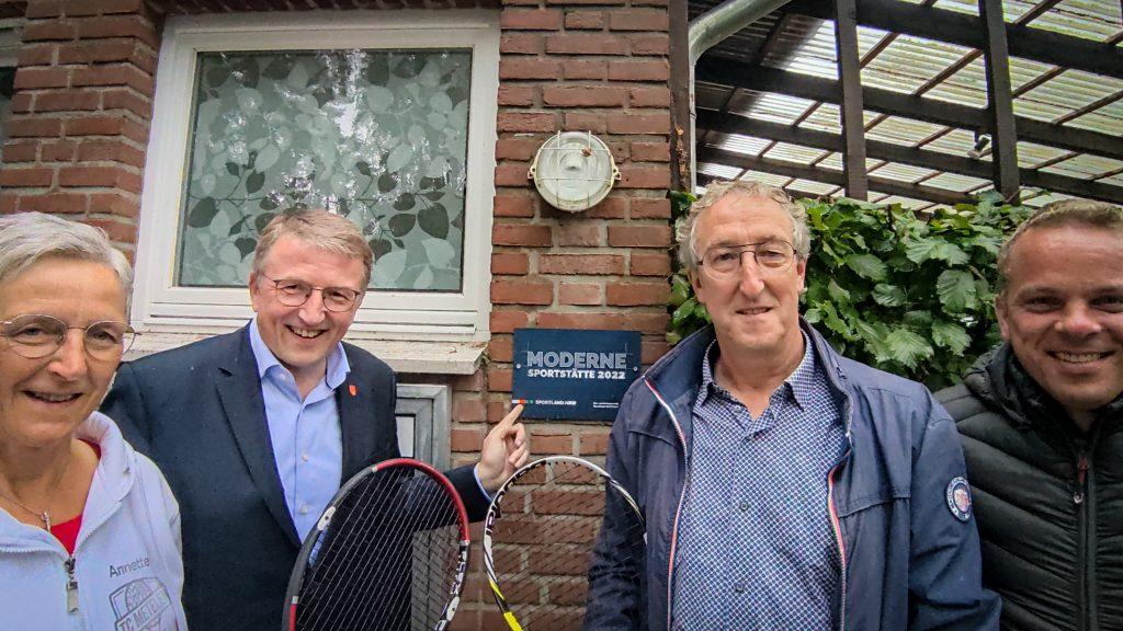 """Das Foto zeigt die Vertreter des Vorstandes vom Tennisverein sowie den Bürgermeister von Metelen vor dem neuen Schild """"Moderne Sportstaette 2022"""""""
